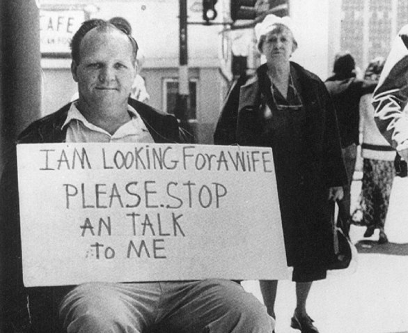 Man holding a sign saying: I am looking for a wife please stop and talk to me