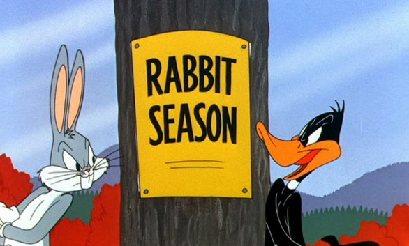 Rabbit Season - Frame from the cartoon rabbit fire showing Duffy and Bugs in front of a sign reading rabbit season