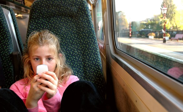 Child using her phone to access the web on a train